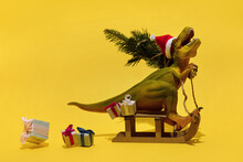 Toy Dinosaur Sitting On Sledge With Gifts And Fir