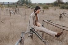 Trendy Woman On Wooden Fence In Field