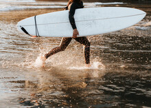 Girl Running With Surfboard