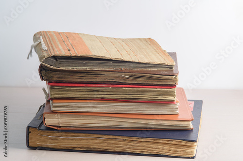 A stack of old faded photo albums or photo books, with yellowed pages on a light background Fototapeta