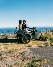 Three Friends In Vintage Sidecar Speaking With Each Other