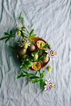 Passionfruit On Plate On Linen With Flowers And Foliage