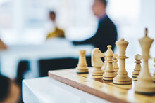 Strategy Chess Battle Intelligence Challenge Game On Board, Cropped Image Of White Figures For Playing With Group Of People On Blurred Background, Concept Of Business Leader And Success Idea