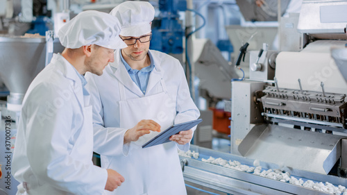 Photo Two Young Male Quality Supervisors or Food Technicians are Inspecting the Automated Production at a Dumpling Food Factory