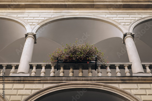 Foto Old arched balcony, baroque style with columns and balustrade and flower pot