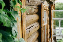 Old Log House. A Corner Of The Facade Of A House With A Window Next To A Green Bush. Close-up