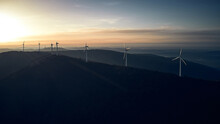 Aerial View Of Sunset Over Mountains And Wind Turbines