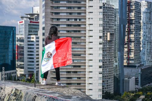 Mujer parada con bandera onservando los edificios Canvas Print