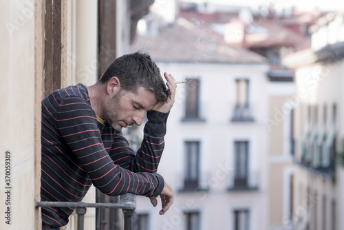 urban lifestyle emotional portrait of young handsome man sad and depressed smoking cigarette thoughtful at home balcony leaning unhappy feeling bittered suffering some problem