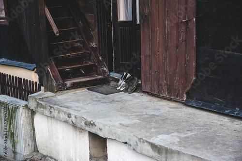 Fototapeta Dwie pary butów wystawione na ganek obok schodów obraz