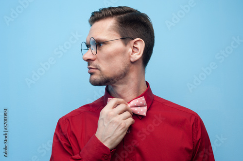 Close-up of the hands of a young man in a red shirt correcting bow-tie against a blue background Fototapete