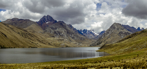 Landscape with moutains, lake, green grass and a moody sky in a hike in Huaraz, Peru