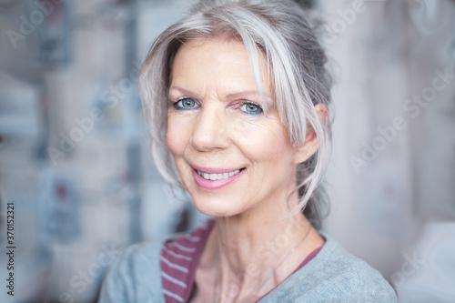 Fototapeta Seniorin mit zufriedenem Lächeln