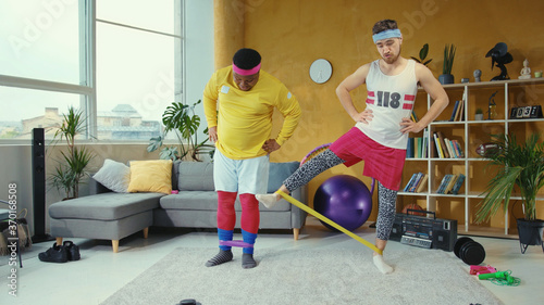 Платно Retro style multi-ethnic men doing home exercising, stretching with elastic bands enjoying workout