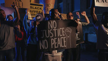 Group Of Multi-ethnic Protests Striking For Human Rights At Night Demonstration. Vigorous Crowd Of Young People Rebelling Against Police Injustice, Racism And Brutality.