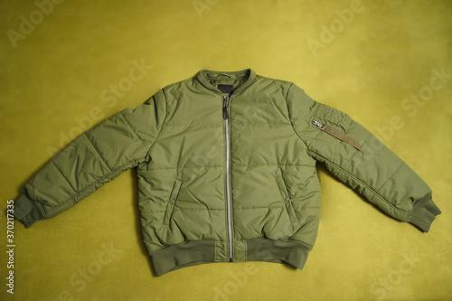 Billede på lærred Khaki casual bomber jacket isolated on green background.