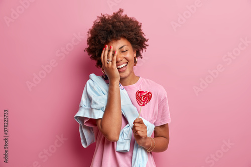 Obraz Positive African American teenage girl makes face palm, has fun, dressed in casual clothes, holds heart shaped lollipop, enjoys spare time, poses against pink background. Confectionery concept - fototapety do salonu