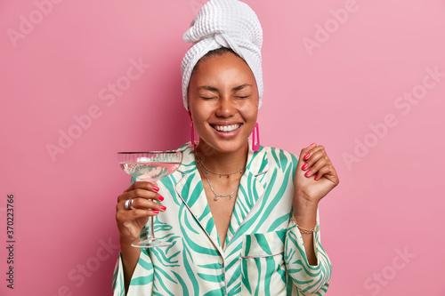 Joyful lady with dark skin, closes eyes and smiles broadly, enjoys free time at Billede på lærred