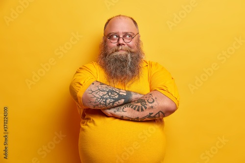 Fototapeta Handsome bearded man keeps arms folded, looks thoughtfully away, has plump body, dressed in casual clothes, makes up plan how to lose weight, isolated over yellow background