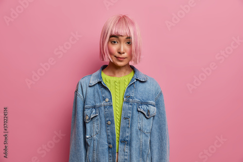 Horizontal shot of attractive young beautiful woman has private conversation, has bob hairstyle, rosy hair wig, dressed in fashionable denim jacket, plans to go out with boyfriend Fotobehang