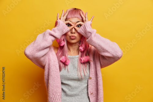 Valokuva Studio shot of lovely surprised woman with pink hair, makes orbs with fingers, w