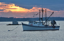 Fading Sunset At Port Clyde, Maine With Floating Lobster Shack And Fishing Trawler Anchored In Calm Harbor.