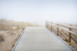 Leinwandbild Motiv Modern wooden pathway to the Baltic sea in a thick white morning fog. Early spring in Latvia. Idyllic rural scene. Nordic walking, recreation, eco tourism, environmental conservation concepts