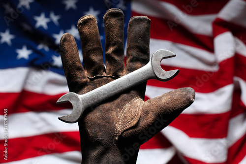 Obraz Hand in worn and dirty golve holding crescent wrench over American Flag - fototapety do salonu