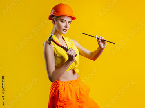 Fotografie, Obraz Young woman hammering nail at workshop on yellow background isolated