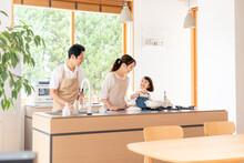 キッチンで料理する家...