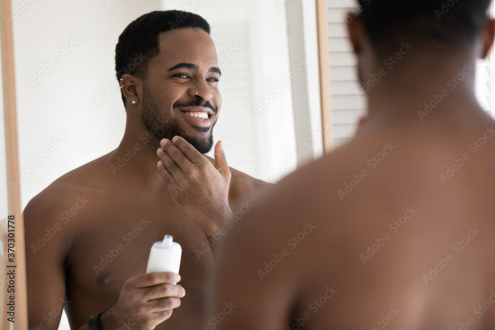 Fototapeta Mirror reflection close up smiling satisfied African American young man applying aftershave moisturizing lotion, standing in bathroom, enjoying skincare routine procedure after shaving