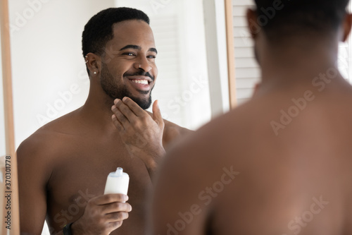 Obraz Mirror reflection close up smiling satisfied African American young man applying aftershave moisturizing lotion, standing in bathroom, enjoying skincare routine procedure after shaving - fototapety do salonu