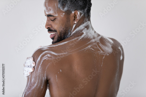 Rear view close up smiling African American handsome young man applying moisturizing gel or shampoo, standing in bathroom, enjoying morning routine skincare procedure, personal hygiene