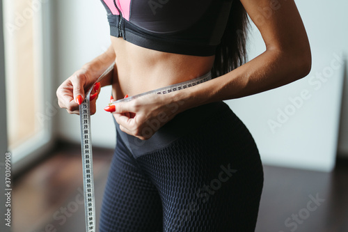 Obraz Fitness motivation and successful weight loss. Woman with perfect slim body measuring her waistline with tape, close up. Diet, home training, healthy lifestyle concept - fototapety do salonu
