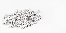 Heap Of Small White Cube Beads With Various Letters Scattered On Board, Space For Text Right Side