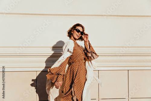 Obraz Pretty woman in long brown dress enjoying sunny day. Lovable white girl in retro attire walking down the street. - fototapety do salonu