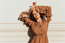 Glamorous Woman In Vintage Dress Posing With Eyes Closed. Outdoor Photo Of Relaxed Female Model In Brown Attire.