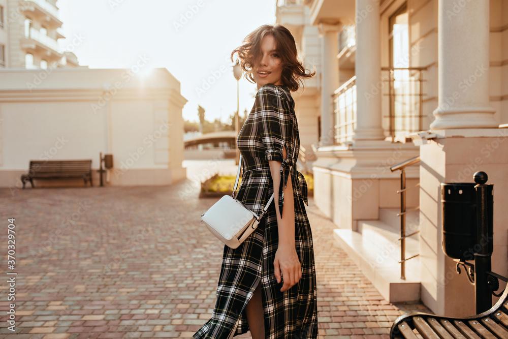 Fototapeta Elegant white girl with little handbag looking back on street background. Pretty curly female model in long dress walking around city in autumn day.
