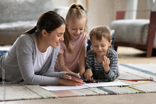 Photo Affectionate loving young mother enjoying painting pictures in paper album with adorable small children siblings