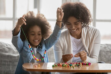 Happy Young African American Mom Have Fun String Colorful Beads Play With Little Ethnic Daughter, Excited Biracial Mother And Small Girl Child Involved In Creative Activity, Make Bracelets Together