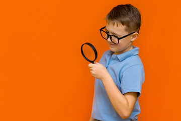 Beautiful european young boy with glasses holding and looking through magnifying glass.Orange wall.