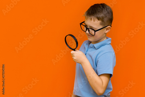 Obraz Beautiful european young boy with glasses holding and looking through magnifying glass.Orange wall. - fototapety do salonu