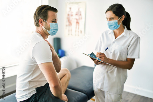 Obraz physiotherapist doing treatment with patient in bright office - fototapety do salonu