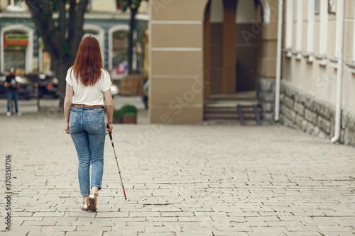 Obraz na plátně Blind woman is walking on the sidewalk in city