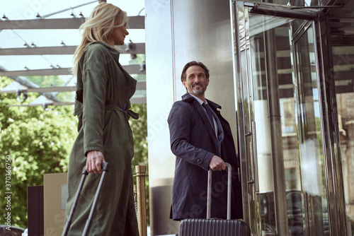 Obraz na plátně Mirthful man with a suitcase holding a hotel door open for his tarvel companion