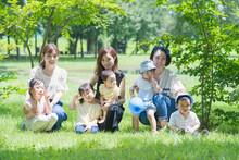 緑あふれる公園で遊ぶ家族たちの集合写真