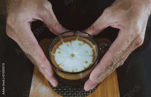 Obraz na plátne close up picture of hands of young man prepare hot cappuccio to serve customer in the cafe