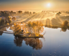 Aerial View Of House With Colorful Trees On Small Island On The Lake. Foggy Sunrise In Autumn. Beautiful Landscape With Village In Fog, Golden Sunbeams, Reflection In Water. Fall In Ukraine. Top View