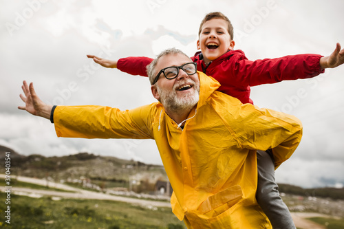 Fototapeta Father giving son piggyback ride outdoors obraz