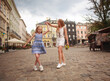 Mother and daughter walk together cheerfully in historic square of old tourist town